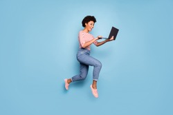 Full length body size side profile photo of pretty cheerful cute nice charming youngster typing before laptop wearing jeans denim striped shirt isolated pastel color blue background