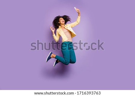 Full length body size turned photo of stylish trendy curly wavy brown hair fashion girl showing ok sign taking selfie jumping in yellow jacket pants trousers isolated pastel color violet background