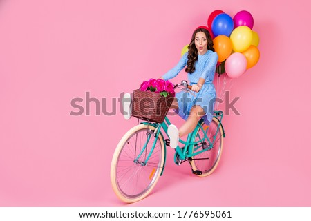 Full length body size view of attractive cheerful cheery wavy-haired lady riding bike without legs delivering celebratory festal decoration having fun grimacing isolated pink pastel color background Foto stock ©
