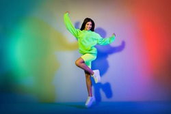 Full length body size view of attractive cheerful girl jumping having fun isolated over multicolor vivid neon light background