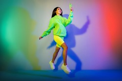 Full length body size view of attractive cheerful girl jumping using device isolated over multicolor vivid neon light background