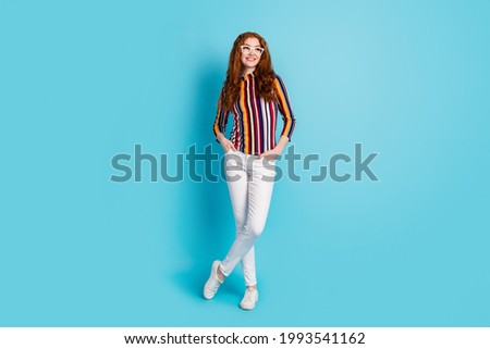 Full length body size view of attractive cheerful girl wearing specs crossed legs thinking copy space isolated over blue color background