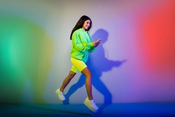 Full length body size view of beautiful trendy girl jumping using gadget chatting isolated over multicolor vivid neon light color background