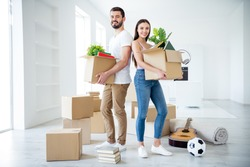 Full length body size view of  couple holding in hands stuff package settling down at place space flat light white interior house indoors