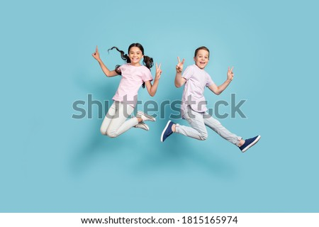 Full length body size view of her she his he nice attractive small little cheerful cheery friends friendship kids jumping showing v-sign having fun isolated over blue pastel color background Photo stock ©