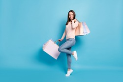 Full length body size view of her she nice attractive cheerful brown-haired girl jumping carrying new things clothes bargain retail outlet isolated bright vivid shine vibrant blue color background