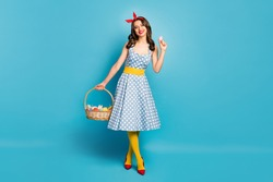 Full length body size view of her she nice attractive lovely pretty fashionable cheerful cheery girl carrying basket colored eggs isolated on bright vivid shine vibrant blue color background