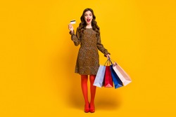 Full length body size view of her she nice attractive rich wealthy amazed cheerful wavy-haired girl holding in hand bag using bank card isolated on bright vivid shine vibrant yellow color background