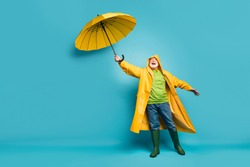 Full length body size view of his he cheerful cheery dreamy grey-haired man wearing yellow topcoat bad cold weather cyclone day isolated over bright vivid shine vibrant blue color background