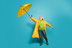 Full length body size view of his he dreamy grey-haired man fisherman wearing yellow topcoat bad weather cyclone wind blowing isolated over bright vivid shine vibrant blue color background