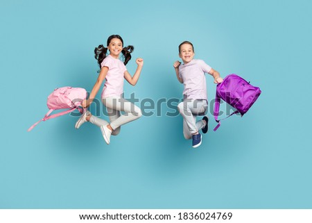 Full length body size view of his he her she nice attractive small little cheerful buddy, fellow jumping having fun after classes leisure autumn fall season isolated blue pastel color background