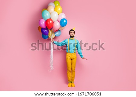 Full length body size view of his he nice attractive cheerful cheery comic bearded guy holding in hands air balls blowing whistle having fun isolated over pastel pink color background