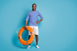 Full length body size view of his he nice attractive cheerful cheery confident guy rescuer carrying rubber lifesaver isolated over bright vivid shine vibrant blue color background