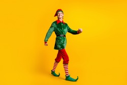 Full length body size view of his he nice attractive cheerful cheery funny guy elf walking having fun christmastime winter party isolated over bright vivid shine vibrant yellow color background