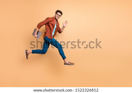 Full length body size view of his he nice attractive cheerful cheery glad content guy jumping in air carrying laptop running fast late hurry-up meeting isolated over beige color pastel background