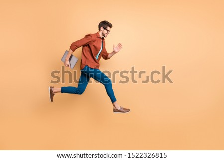 Full length body size view of his he nice attractive cheerful cheery successful brunet guy jumping in air carrying laptop running fast late hurry-up isolated over beige color pastel background