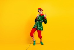 Full length body size view of his he nice attractive cool naughty funny guy elf singing hit having fun showing horn symbol isolated over bright vivid shine vibrant yellow color background