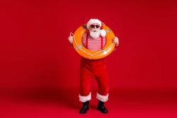Full length body size view of his he nice handsome cheery funny bearded Santa father instructor wear sea ocean pool safe circle resort leisure isolated bright vivid shine vibrant red color background