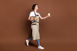 Full length body size view of lovely cheerful girl carrying bringing coffee time break isolated over brown color background