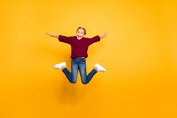 Full length body size view of nice attractive carefree glad girlish cheerful cheery pre-teen girl jumping having fun flying like plane isolated on bright vivid shine vibrant yellow color background