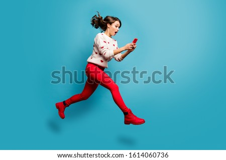 Full length body size view of nice attractive cheerful amazed impressed girl jumping using 5g like follow subscribe running hurry rush isolated on bright vivid shine vibrant blue color background Foto stock ©