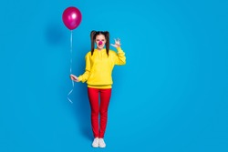 Full length body size view of nice attractive creepy evil mad aggressive girl circus clown holding in hand helium ball pretending attack isolated over bright vivid shine vibrant blue color background