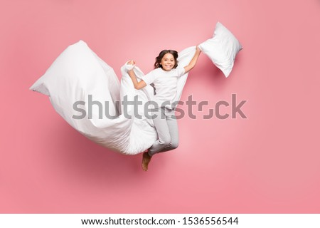 Full length body size view of nice attractive cute playful cheerful cheery wavy-haired pre-teen girl jumping flying with soft cotton pillow blanket isolated over pink pastel color background