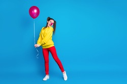 Full length body size view of nice attractive, funny delighted glad cheerful cheery girl clown holding in hand air ball having fun occasion isolated on bright vivid shine vibrant blue color background
