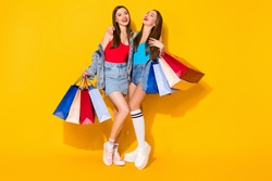 Full length body size view of nice attractive lovely charming cheerful cheery brown-haired girls carrying new things clothes having fun isolated on bright vivid shine vibrant yellow color background