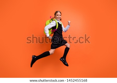Full length body size view of nice attractive lovely cheerful cheery glad diligent pre-teen girl nerd running fast first grade back to school isolated on bright vivid shine orange background