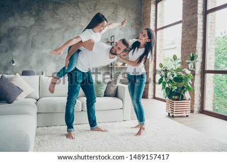 Full length body size view of nice attractive lovely cheerful cheery glad family wearing casual white t-shirts jeans having fun fooling spending time at industrial loft style interior living-room
