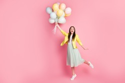 Full length body size view of nice attractive pretty fashionable glad cheerful cheery girl holding in hands air balls aving fun flying up isolated on bright vivid shine vibrant yellow color background