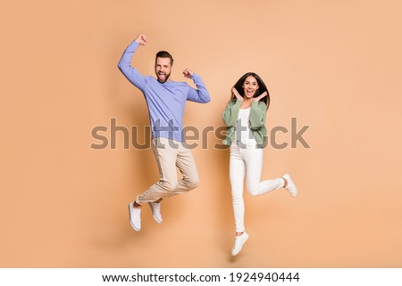 Full length body size view of nice cheerful lucky partners couple jumping having fun isolated on beige pastel color background