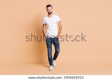 Full length body size view of nice content attractive tall macho guy going isolated over beige pastel color background Foto d'archivio ©