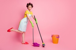 Full length body size view of pretty amazed funky girlish maid cleansing sweeping floor dust pout lips isolated on pink pastel color background