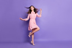 Full length body size view of pretty cheery girl dancing relax wind blowing hair isolated over bright violet color background