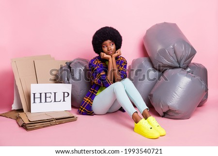 Full length body size view of pretty miserable girl sitting with stack waste help card waiting isolated over pink pastel color background
