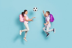 Full length body size view of two attractive small little cheerful friends friendship jumping play soccer cup goal throwing ball hobby leisure isolated blue pastel color background