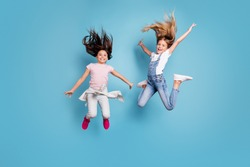 Full length body size view of two people nice crazy attractive cheerful carefree careless straight-haired pre-teen girls having fun great cool day free time overjoy isolated on blue background