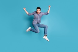 Full length body size view photo cute nice youth raise fists scream yeah celebration wonderful news thrilled satisfied candid checked shirt jeans sneakers weekend holidays isolated blue background
