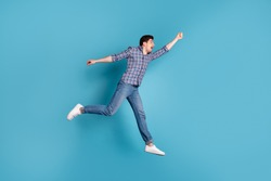Full length body size view photo of frightened millennial hold hand hang hanger scream shout wind blows dressed fashionable checkered clothing denim sneakers isolated on blue background