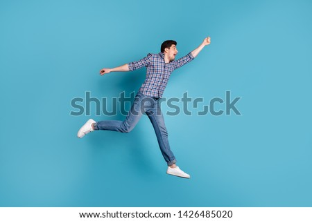 Full length body size view photo of frightened millennial hold hand hang hanger scream shout wind blows dressed fashionable checkered clothing denim sneakers isolated on blue background #1426485020