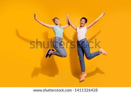 Full length body size view photo of positive cheerful satisfied nice student teenager hold hand free time enjoy excited trendy style stylish jeans clothes isolated wavy curly hairdo yellow background