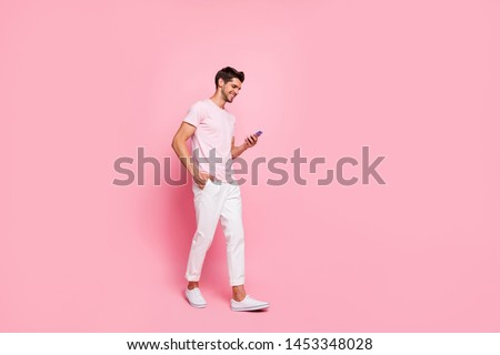 Full length body size view portrait of his he nice attractive content cheerful cheery guy walking enjoying free spare time isolated over pink pastel background