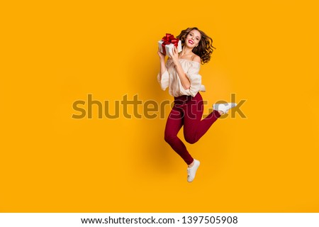 Full length body size view portrait of nice-looking attractive pretty slim fit thin glad cheerful cheery wavy-haired lady holding in hands box isolated over bright vivid shine yellow background