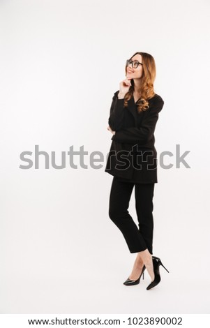 Full-length businesslike woman in total black outfit and eyeglasses smiling and looking upward on copyspace isolated over white background