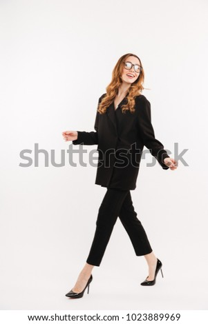 Full-length businesswoman with brown curls wearing black clothes and eyeglasses smiling and walking along white background