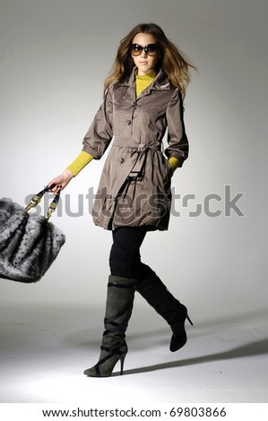 Full length casual young fashion model holding bag posing