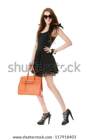 Full length casual young model in sunglasses holding bag posing