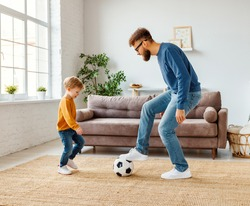 Full length cheerful boy laughing   near bearded father with ball while playing football at home together